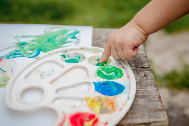 Netter kleiner junge, der mit einer farbe hände unter verwendung von gauche-farben malt.
