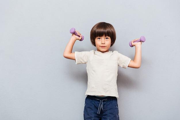 Netter kleiner junge, der mit hanteln steht und trainiert