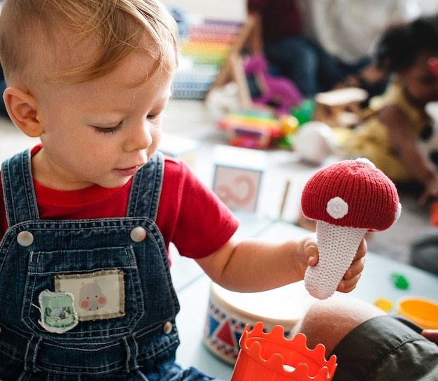 Netter kleiner junge, der mit spielwaren im lernzentrum spielt