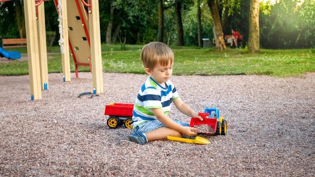 Netter kleiner junge, der mit spielzeug auf dem spielplatz spielt. kind hat spaß mit lkw, bagger und anhänger