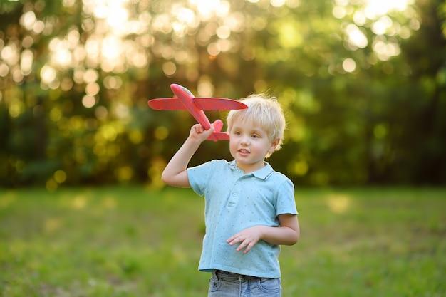 Netter kleiner junge, der mit spielzeugflugzeug im sonnigen park spielt.