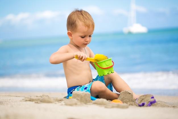 Netter kleiner junge, der mit strandspielzeug am tropischen strand spielt