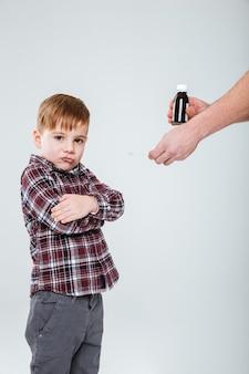 Netter kleiner junge, der mit verschränkten armen steht und sich weigert, eine medizin zu nehmen