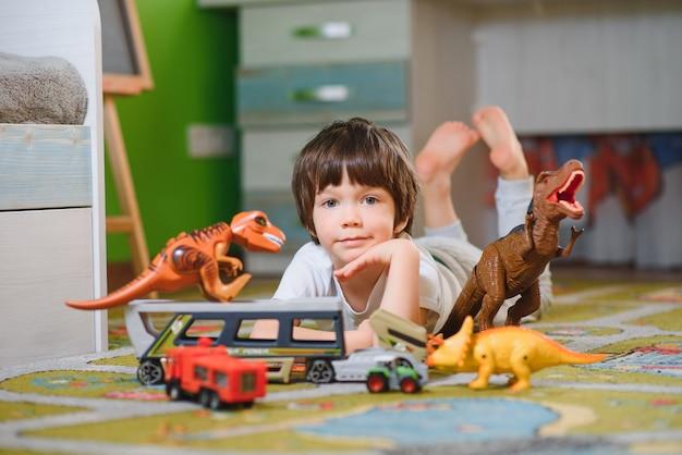 Netter kleiner junge, der mit vielen spielzeugautos drinnen spielt. glücklicher vorschulkind, der spaß zu hause oder im kindergarten hat