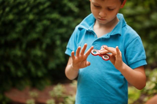 Netter kleiner junge, der mit zappelhandspinner am sommertag spielt. beliebtes und trendiges spielzeug für kinder und erwachsene.