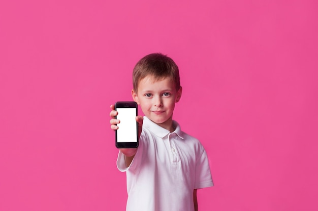 Netter kleiner junge, der mobiltelefon des leeren bildschirms auf rosa hintergrund zeigt