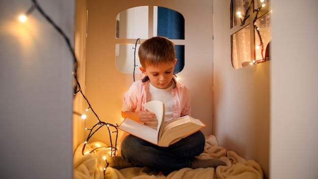 Netter kleiner junge, der nachts im spielzeugpappehaus sitzt und ein großes märchenbuch liest. konzept der kindererziehung und des lesens in der dunkelkammer.