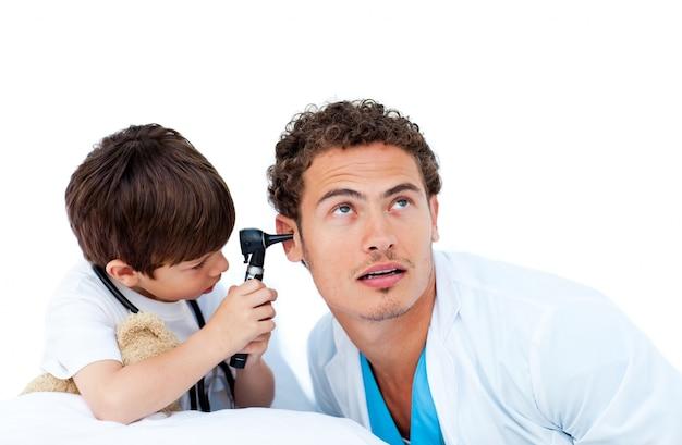Netter kleiner junge, der ohren doktors überprüft