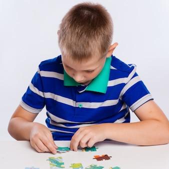 Netter kleiner junge, der puzzlespiele am tisch spielt