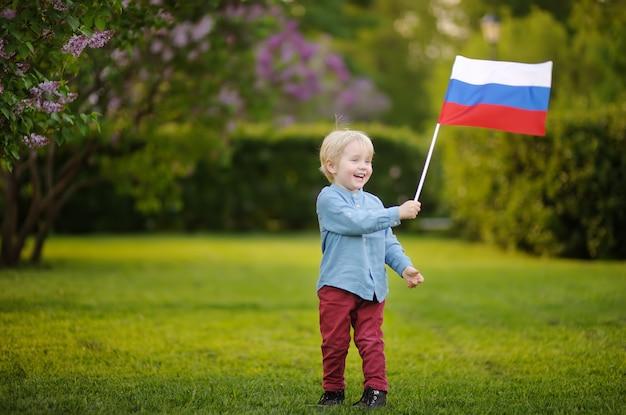Netter kleiner junge, der russische flagge während des gehens in sommerpark hält