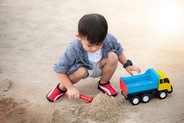 Netter kleiner junge, der sand mit spielzeuglastwagen auf dem strand spielt