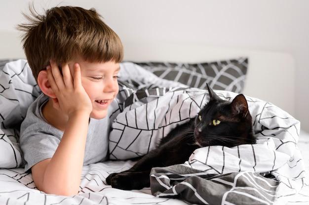 Netter kleiner junge, der seine katze beobachtet