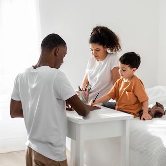 Netter kleiner junge, der seine vaterhand auf papier zeichnet, während er im bett sitzt