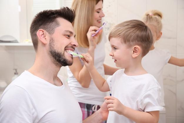 Netter kleiner junge, der seinem vater beim zähneputzen im badezimmer hilft