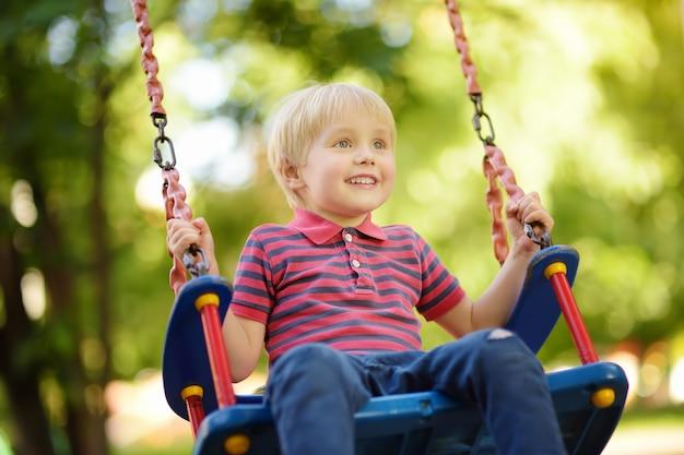 Netter kleiner junge, der spaß auf spielplatz im freien hat. kind auf schaukel