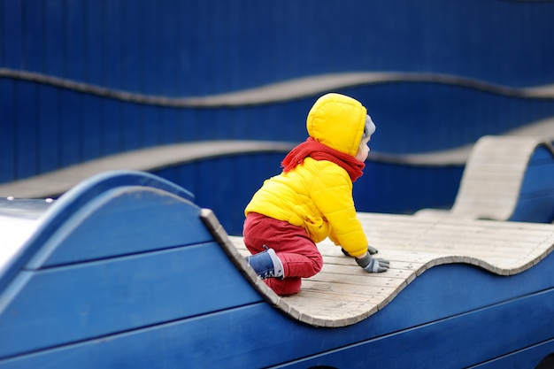 Netter kleiner junge, der spaß auf spielplatz im freien hat