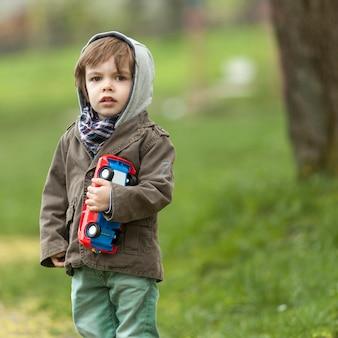 Netter kleiner junge, der spielzeugauto hält