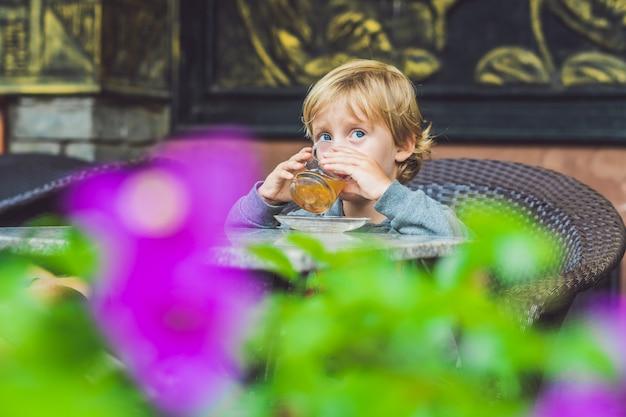 Netter kleiner junge, der tee in der cafeteria trinkt