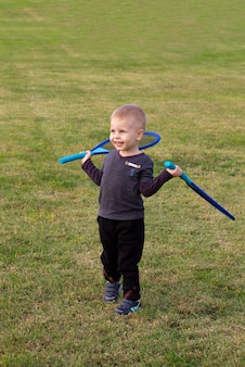 Netter kleiner junge, der tennis auf dem platz spielt