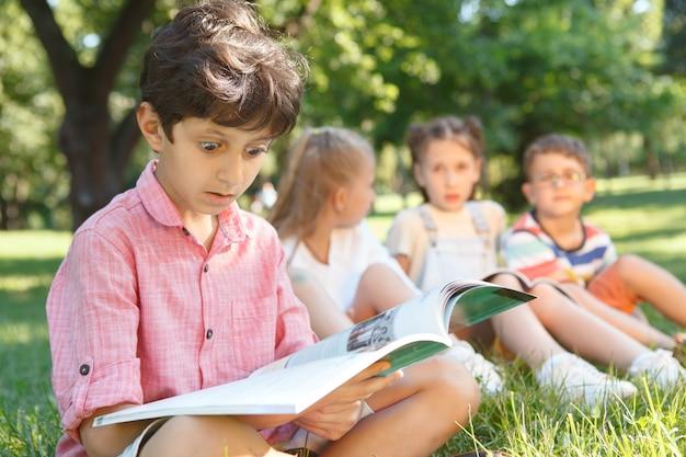 Netter kleiner junge, der überwältigt aussieht und ein buch im öffentlichen park liest