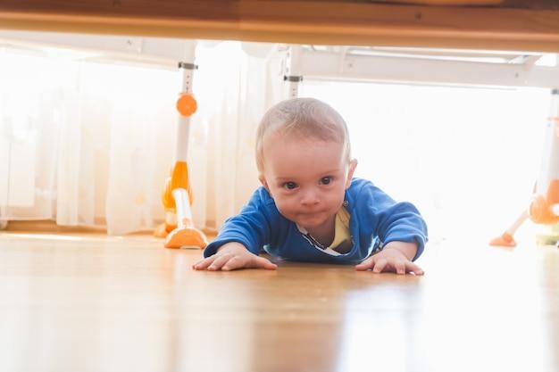 Netter kleiner junge, der unter das bett krabbelt und schaut