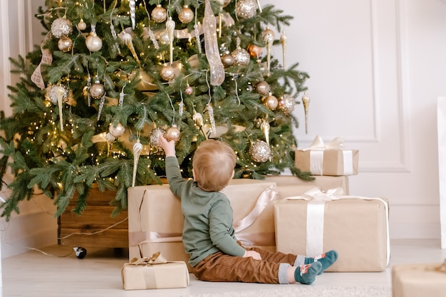 Netter kleiner junge, der unter weihnachtsbaum mit geschenkbox sitzt.