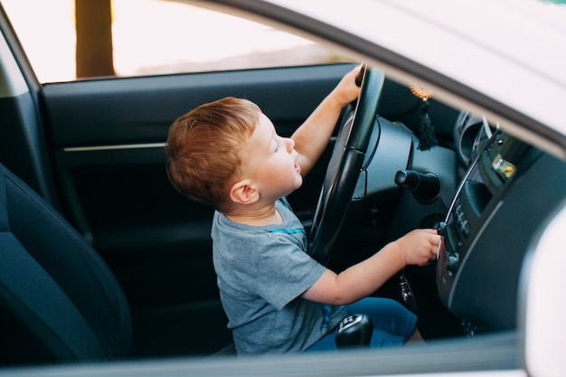 Netter kleiner junge, der väterauto fährt