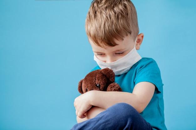 Netter kleiner junge, der vernebler auf blau verwendet. allergiekonzept