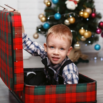 Netter kleiner junge, der versteckt in einem roten karierten koffer spielt