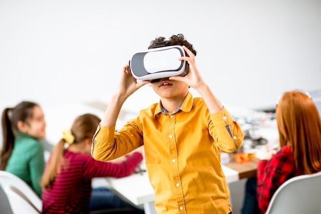 Netter kleiner junge, der vr virtual-reality-brille in einem robotik-klassenzimmer trägt