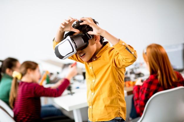 Netter kleiner junge, der vr-virtual-reality-brille in einem robotik-klassenzimmer trägt