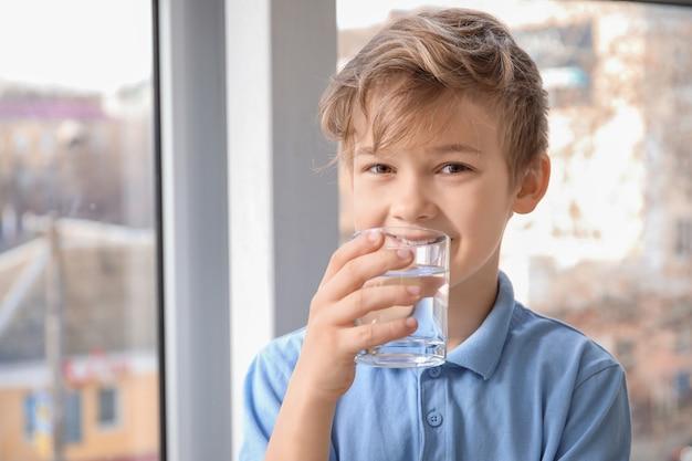 Netter kleiner junge, der wasser nahe fenster trinkt