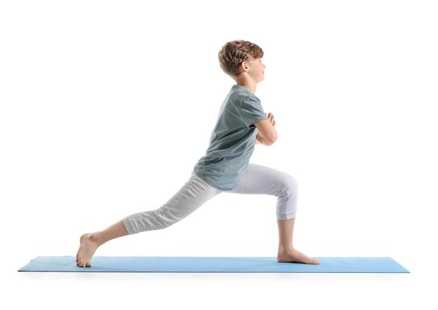 Netter kleiner junge, der yoga auf weiß praktiziert