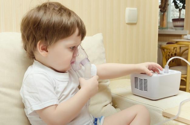 Netter kleiner junge, der zu hause auf der couch sitzt und durch einen zerstäuberinhalator atmet. der junge heilt den husteninhalator.
