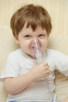 Netter kleiner junge, der zu hause auf der couch sitzt und durch einen zerstäuberinhalator atmet.