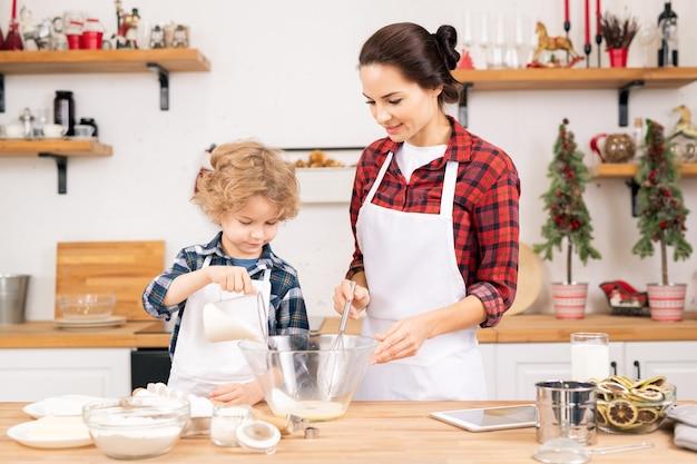 Netter kleiner junge, der zucker in geschüttelte rohe eier in der schüssel hinzufügt, während er seiner mutter mit teig für hausgemachtes gebäck in der küche hilft