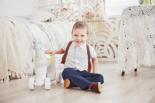 Netter kleiner junge geht zum ersten mal zur schule. kind mit schultasche und buch. kid macht eine aktentasche, kinderzimmer. zurück zur schule
