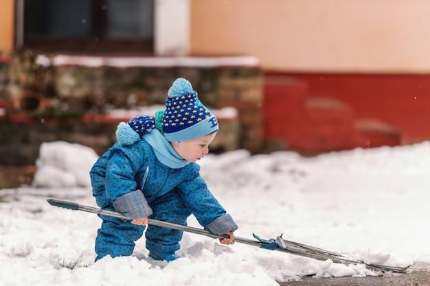 Netter kleiner junge gekleidet in der blauen winterkleidung, die mit heugabel auf dem schnee spielt.