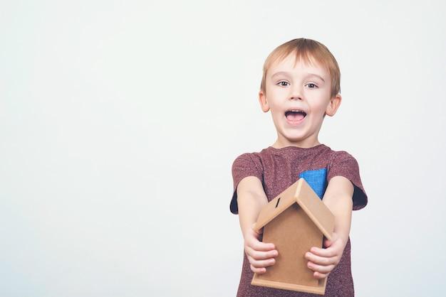 Netter kleiner junge hält eine kleine hausbank und konzepte, die geld für haus und zukunft sparen.