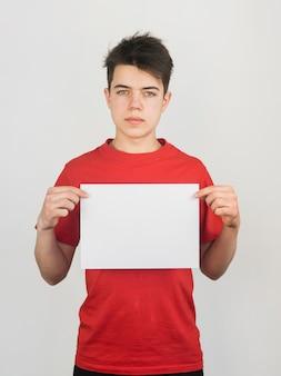 Netter kleiner junge im roten t-shirt, der eine kopie raumpapier hält