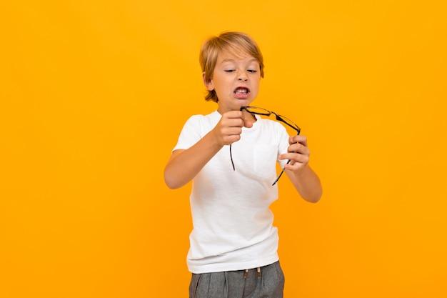 Netter kleiner junge im t-shirt und in der hose hält eine brille lokalisiert auf gelbem hintergrund