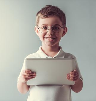 Netter kleiner junge in den brillen hält eine digitale tablette.