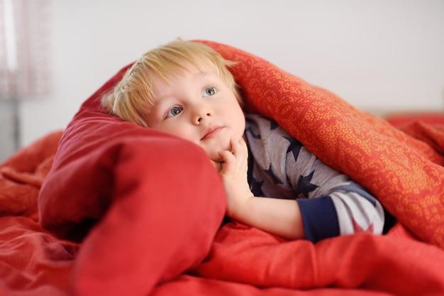 Netter kleiner junge in den pyjamas, die spaß im bett nachdem dem schlafen und fernsehen oder träumen haben
