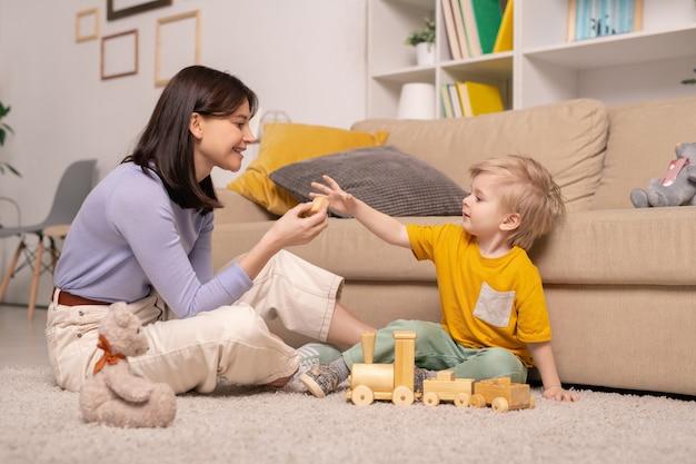Netter kleiner junge in der freizeitkleidung, der auf dem boden durch couch sitzt und spielzeugwürfel von der hand seiner mutter nimmt, während mit holzzug spielt