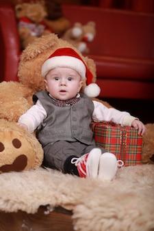 Netter kleiner junge in der weihnachtsmannmütze mit großem teddybär und weihnachtsgeschenken.