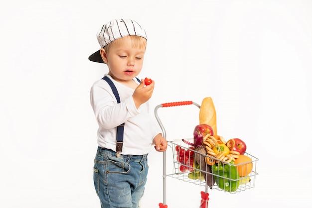 Netter kleiner junge in der zufälligen kleidung, die im studio mit gesundem lebensmittelkorb steht. einkaufen, rabatt, verkaufskonzept