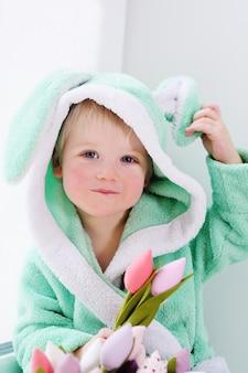 Netter kleiner junge in einem kaninchenkostüm mit einem blumenstrauß am muttertag.