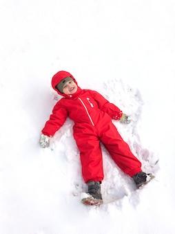 Netter kleiner junge in einem roten winteroverall im winter auf der straße macht einen schneeengel und hat spaß.