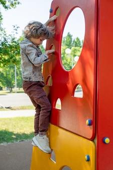 Netter kleiner junge in gekreuzten schuhen, jeansjacke und hose, die am sommertag auf freizeiteinrichtungen für kinder im park klettern oder absteigen