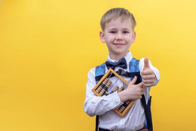 Netter kleiner junge in uniform mit rucksack auf gelb